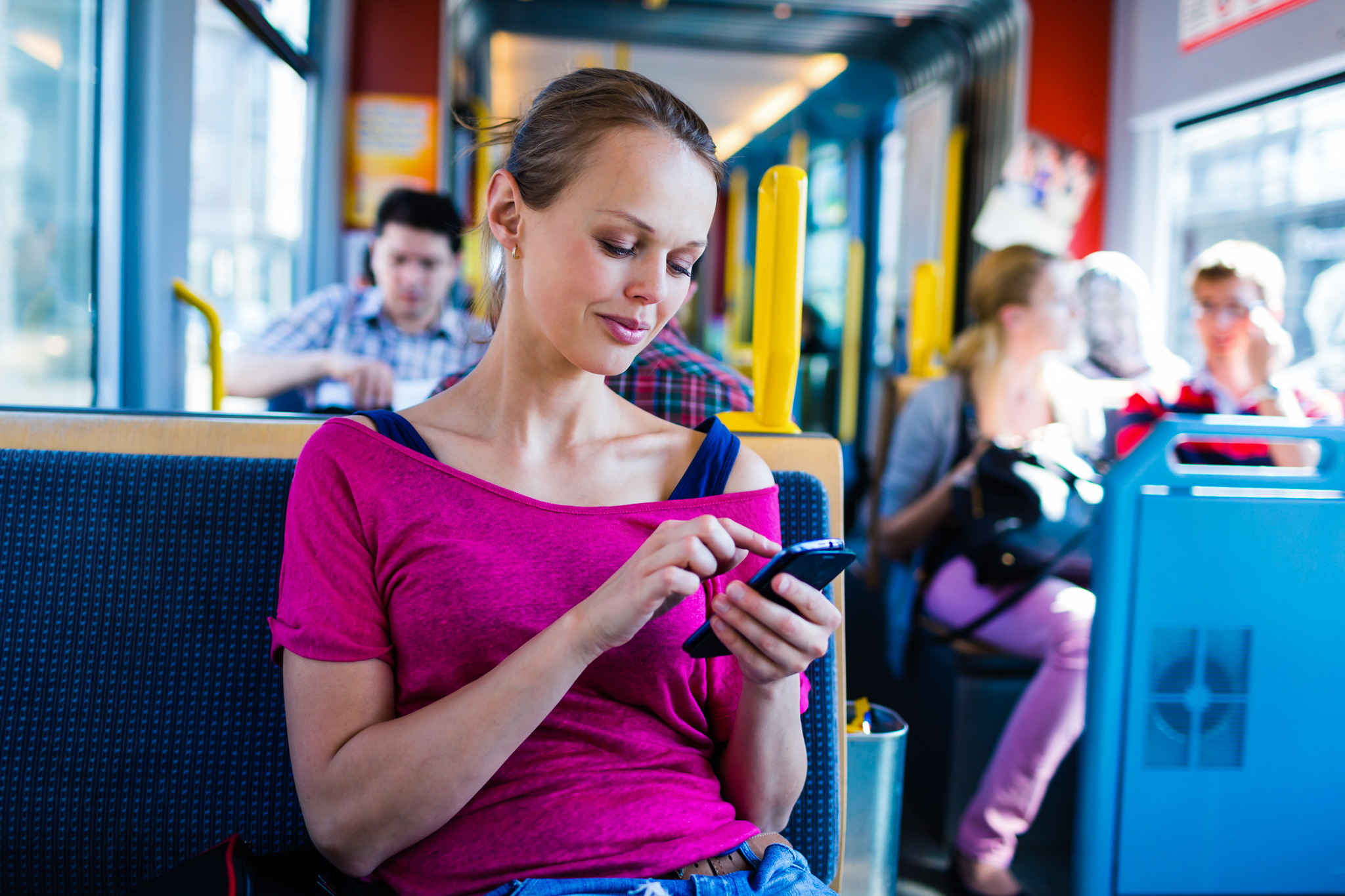 Young woman using a smartphone on a tram