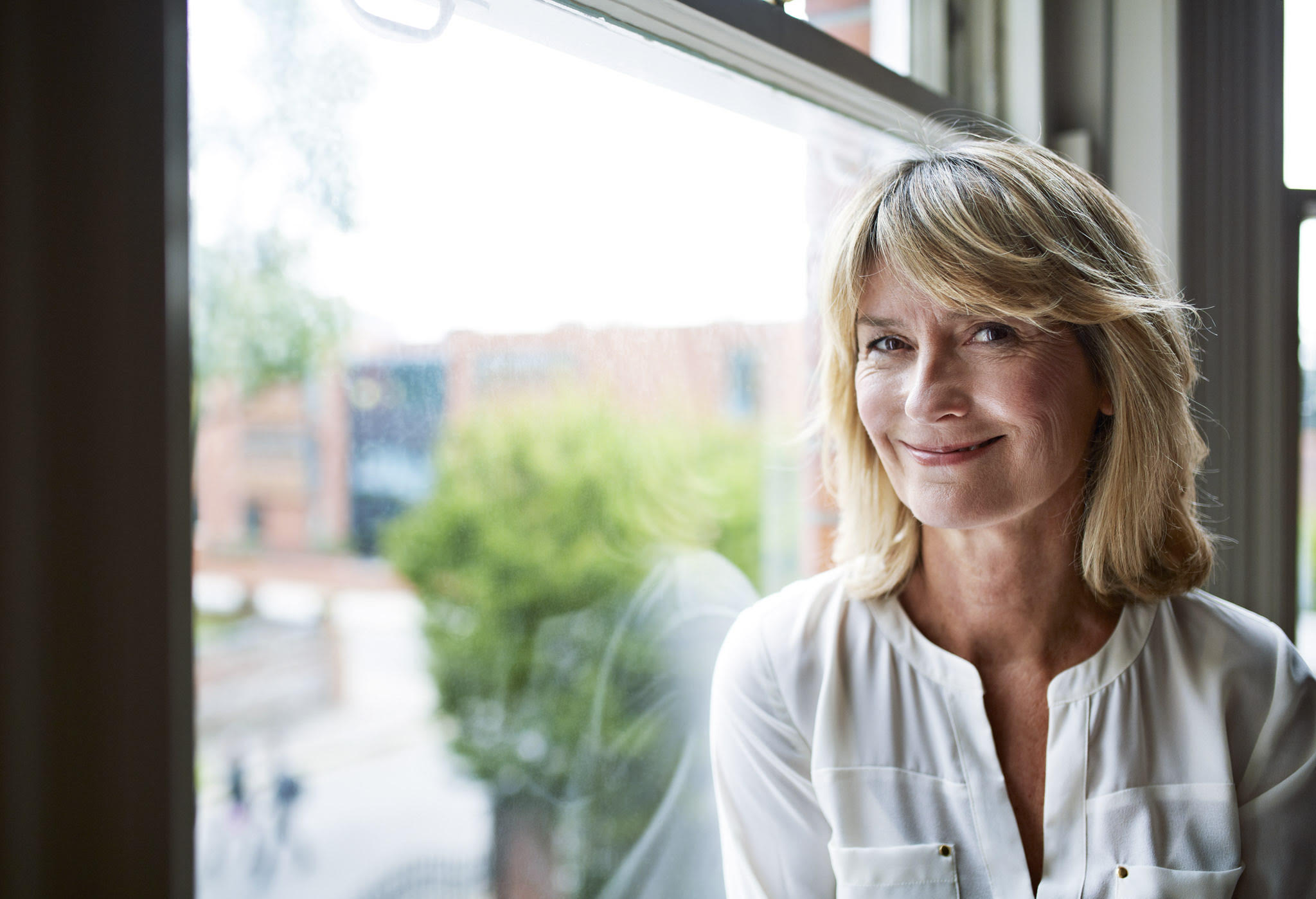Portrait of a smiling mature woman sitting by a window at home